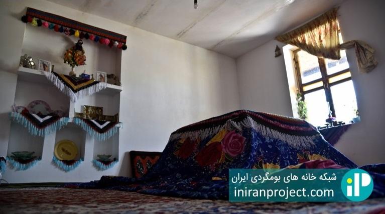 تصویری از نمای داخلی خانه بومگردی باجیلار و کرسی در آن